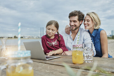 Germany, Duesseldorf, happy family with daughter using laptop on wooden table at Rhine riverbank - RORF01709
