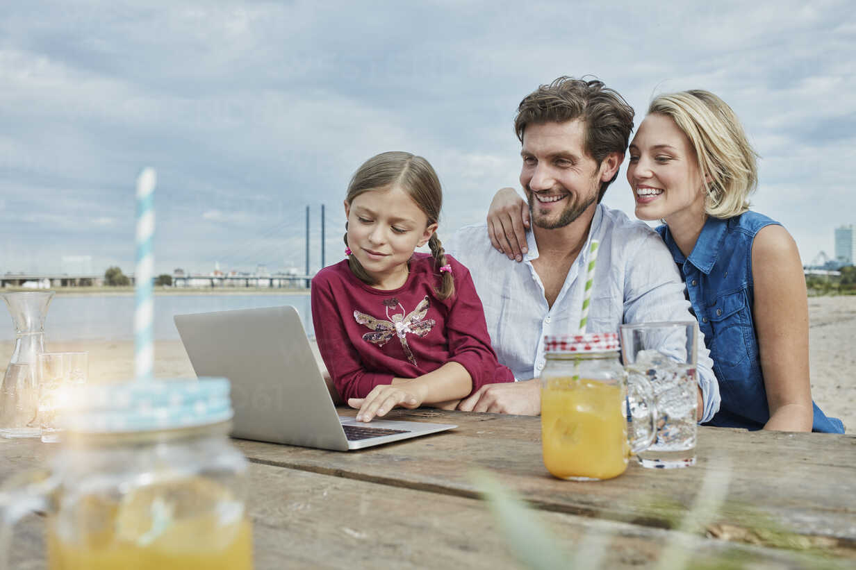 Germany, Duesseldorf, happy family with daughter using laptop on wooden table at Rhine riverbank - RORF01709 - Roger Richter/Westend61