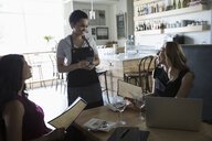Businesswomen ordering from waitress at cafe - HEROF15080