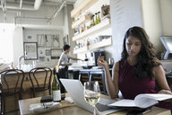Businesswoman drinking wine and reviewing paperwork, working at laptop in cafe - HEROF15086