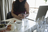 Businesswoman with smart phone and laptop working in cafe - HEROF15092