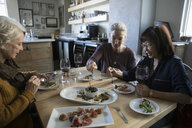 Active senior women friends eating appetizers and drinking red wine in cafe - HEROF15098