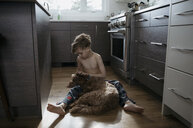 Affectionate bare chested boy cuddling, petting dog on kitchen floor - HEROF15113