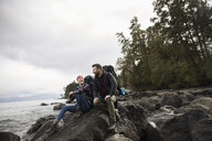 Couple hikers sitting on rocks on rugged beach - HEROF15146