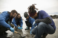 Eco-friendly scientists gathering micro plastic specimens on beach - HEROF15152