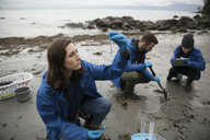 Curious eco-friendly female scientist gathering water specimens on beach - HEROF15155
