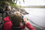 Curious active senior hiker friends using binoculars - HEROF15173