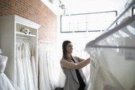 Bride shopping for wedding dresses in bridal boutique - HEROF15191