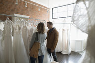 Bride and groom shopping for wedding dresses in bridal boutique - HEROF15200