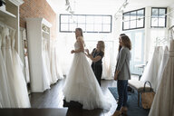 Bride and friends at wedding dress fitting in bridal boutique - HEROF15203