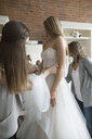 Bride and friends at wedding dress fitting in bridal boutique - HEROF15209