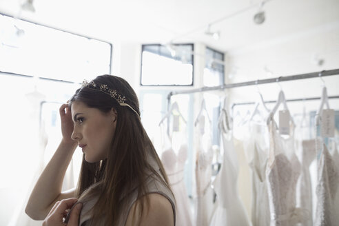 Bride trying on headband at bridal boutique - HEROF15221