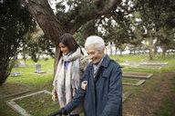 Daughter walking with senior mother in cemetery - HEROF15233