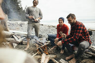Barefoot friends enjoying beers by campfire on rugged beach - HEROF15284