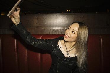 Confident, cool female millennial taking selfie with smart phone in nightclub - HEROF15302