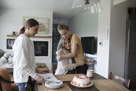 Affectionate teenage daughters hugging and surprising mother with cake - HEROF15308