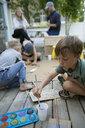 Family making lemonade and painting cardboard lemonade stand in back yard - HEROF15329