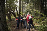 Trail guide with map guiding active senior hikers in woods - HEROF15371