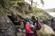 Trail guide showing cave to active senior hiker friends - HEROF15374