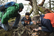 Trail guide teaching father and son how to build campfire in woods - HEROF15377