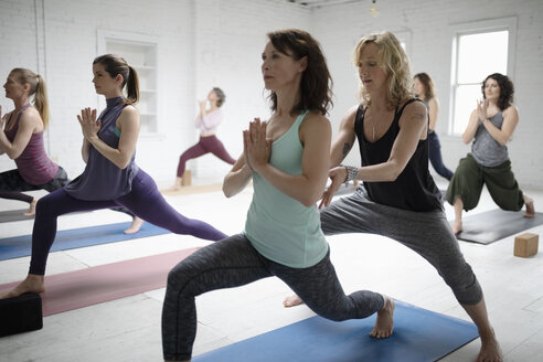 Yoga instructor guiding woman practicing warrior one pose - HEROF15404