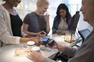 Young women with smart phone paying with contactless payment in boutique - HEROF15437