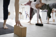 Women practicing half moon pose with blocks in yoga class - HEROF15449