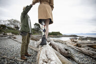 Young man holding hands with amputee girlfriend walking on beach driftwood - HEROF15482