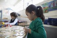 Focused preschool girl assembling jigsaw puzzle in classroom - HEROF15638