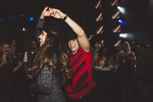 Happy young millennial couple dancing on nightclub dance floor - HEROF15677