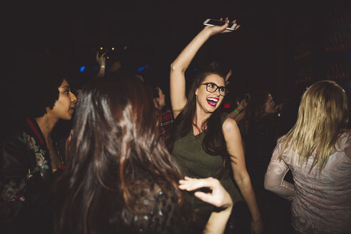 Happy, exuberant young millennial woman dancing, partying at nightclub - HEROF15680