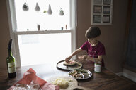 Focused boy making homemade pizza at dining table - HEROF15695