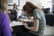 Girl painting fingernails with fingernail polish in living room - HEROF15704