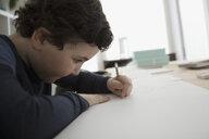 Focused boy sketching, drawing on paper - HEROF15713