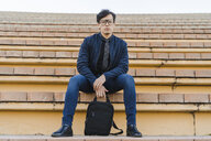 Portrait of fashionable young businessman with backpack sitting on stairs - AFVF02326