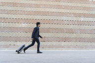 Running young businessman with rolling suitcase - AFVF02335