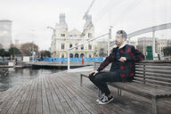 Young man wearing casual clothes sitting on a bench at harbour - JRFF02549