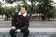 Young man wearing casual clothes sitting on a bench in the city - JRFF02552