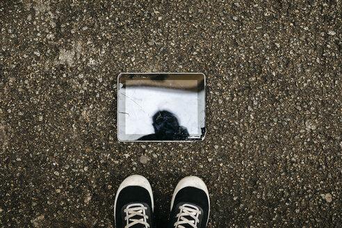 Aerial view of a broken tablet on the floor - JRFF02558