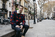 Young man wearing casual clothes sitting on a bench in the city - JRFF02567