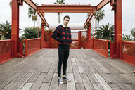 Young man with casual clothes on a red bridge looking at camera - JRFF02570