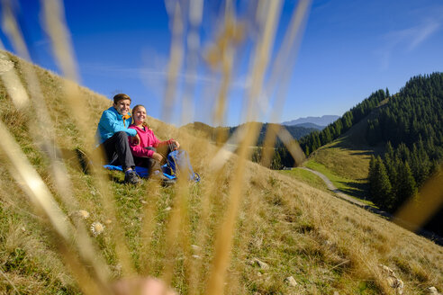 Germany, Bavaria, Hoernle near Bad Kohlgrub, happy young couple having a break sitting in meadow in alpine landscape - LBF02345