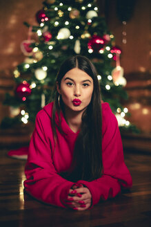 Portrait of teenage girl lying on the floor in front of Christmas tree  pouting mouth - ACPF00415
