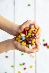 Colourful sweet jellybeans in hands, forming a heart - SARF04083