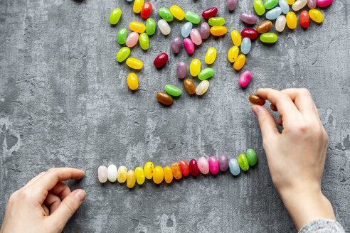 Row of colourful sweet jellybeans on gray background - SARF04086