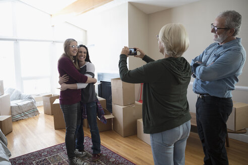 Parents with camera phone photographing lesbian couple moving into new house - HEROF15755