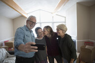 Parents helping affectionate lesbian couple move into new house, taking selfie - HEROF15761
