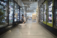 Male worker restocking refrigerated case in grocery store - HEROF15815