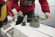 Man adjusting rigging rope on sailboat - HEROF15875