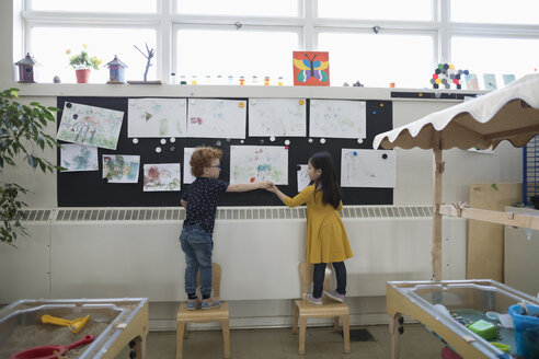 Preschool boy and girl hanging paintings on wall in classroom - HEROF15965